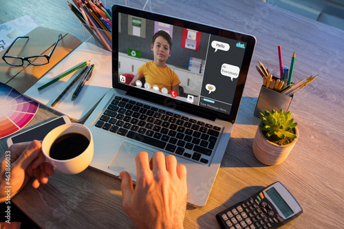 Hands of man using laptop for video call, with caucasian elementary school pupil on screen