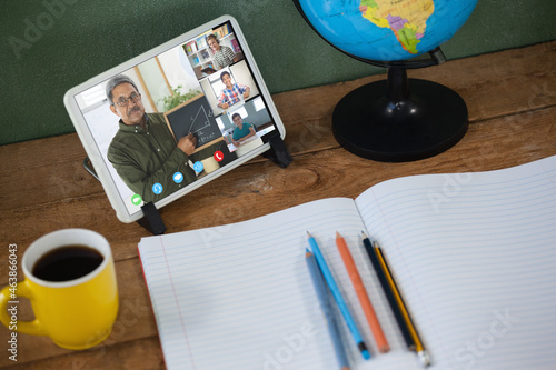Smiling biracial male teacher with smiling diverse elementary school pupils on tablet screen