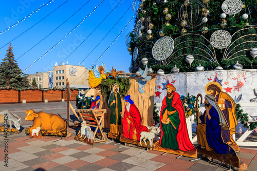 Fototapeta Wooden Christmas Nativity scene with Holy family in city park
