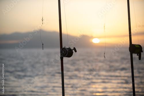 Fototapeta Fishing rod and reel on the sea and sunset sky.