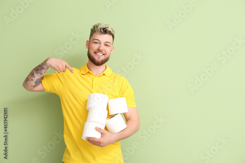 Fotografiet Young man with many rolls of toilet paper on color background