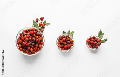 Bowls with fresh rose hip berries on white background