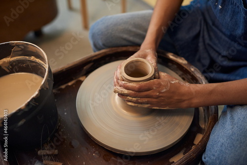 Fotografia Close-up of unrecognizable potter sitting at pottery wheel and creating ceramic