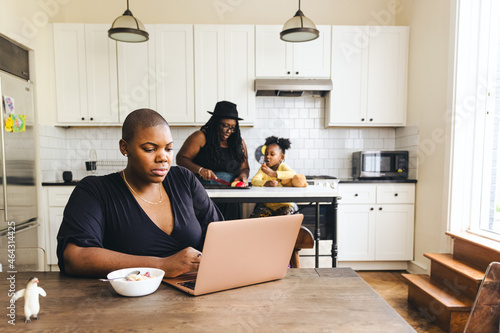 Tela Female freelancer working on laptop while girlfriend and daughter prepare food i