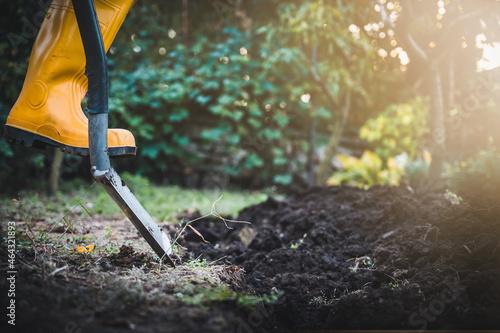Murais de parede Worker digs soil with shovel in colorful garden, agriculture concept autumn detail