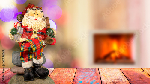 Fotografiet Santa Claus doll on the table and colorful blurred background with lights and fireplace