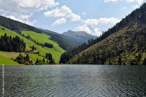Tela Lago di Valdurna in AltoAdige cielo serene e riflessi sulla superficie, chiesa t