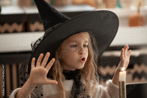 Obraz na płótnie A girl in a witch hat conjures a candle, a child is dressed in a costume for a h