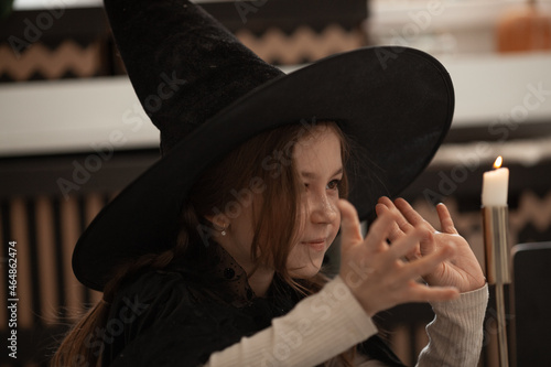 A girl in a witch hat conjures a candle, a child is dressed in a costume for a h Fototapeta